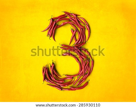 3D rendering of number three formed with chili peppers on a yellow background - stock photo