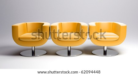 3D rendering of three modern yellow leather armchairs in a row - stock photo