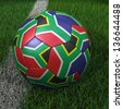 3D soccer ball with South Africa flag on green field. - stock photo