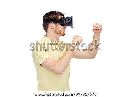 3d technology, virtual reality, entertainment and people concept - young man with virtual reality headset or 3d glasses playing game and fighting