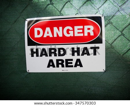 danger hard hat area sign on fence