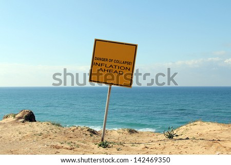 Danger  of collapse! Inflation ahead! A sign on the edge of a hill overlooking the sea: The sign warns: Danger, Stay Back, Unstable Cliffs,  Keep Out - stock photo