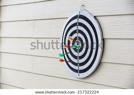 dart board arrows missed target on wood wall of public - stock photo