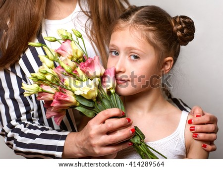 daughter gives her mother flowers in the studio, happy mother's dayâ?¨ - stock photo