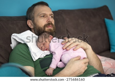 14-day baby sleeping on the stomach of his father with a beard - stock photo