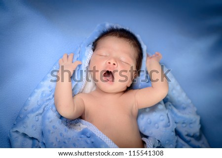 5 day old baby boy plays joyfully in blue blankets - stock photo
