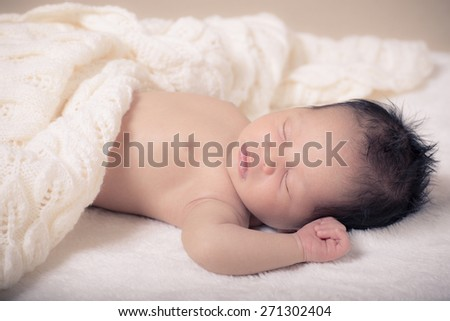10 day old mixed race Asian Caucasian baby boy sleep peacefully on white fluffy blankets