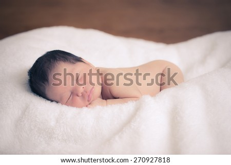5 day old mixed race Asian Caucasian newborn baby boy sleeps peacefully on thick soft blankets.