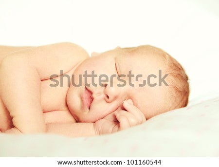 12 days old child sleeping on the side in bed