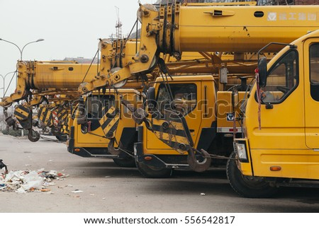 14,Dec,2014 - Beijing China,Yellow Crane trucks,on the road beside rubbish
