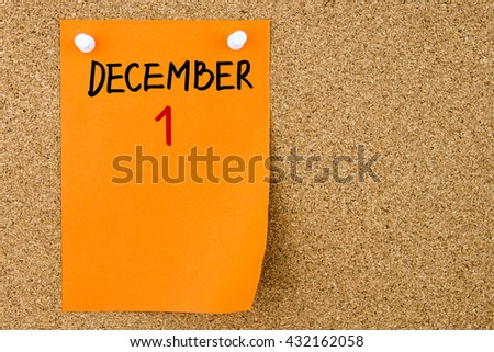 1 DECEMBER written on orange paper note pinned on cork board with white thumbtacks, copy space available - stock photo