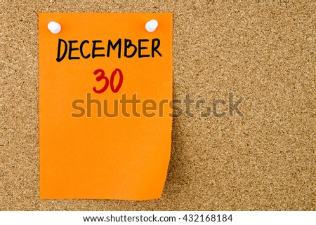 30 DECEMBER written on orange paper note pinned on cork board with white thumbtacks, copy space available - stock photo