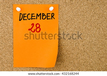 28 DECEMBER written on orange paper note pinned on cork board with white thumbtacks, copy space available - stock photo