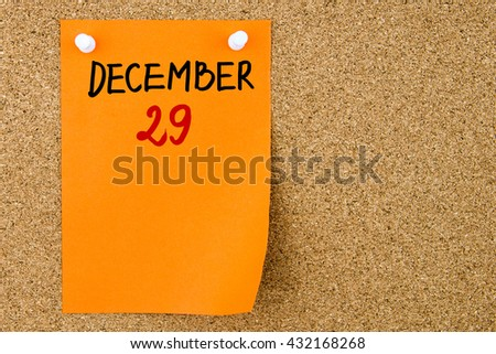 29 DECEMBER written on orange paper note pinned on cork board with white thumbtacks, copy space available - stock photo