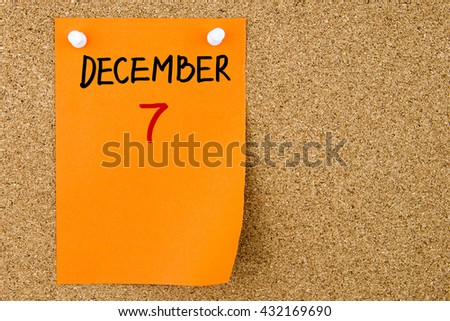 7 DECEMBER written on orange paper note pinned on cork board with white thumbtacks, copy space available - stock photo