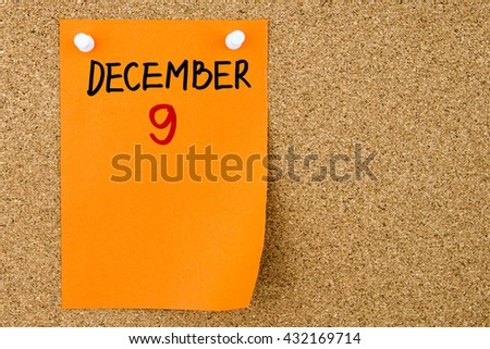 9 DECEMBER written on orange paper note pinned on cork board with white thumbtacks, copy space available - stock photo