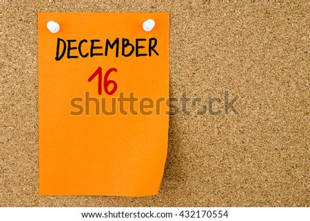 16 DECEMBER written on orange paper note pinned on cork board with white thumbtacks, copy space available - stock photo