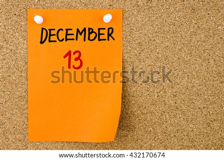 13 DECEMBER written on orange paper note pinned on cork board with white thumbtacks, copy space available - stock photo