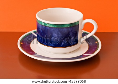 decorative tea cup on brown and orange background