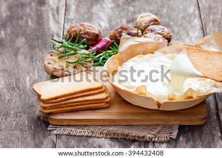 Delicious baked camembert with roasted potato and toasts - stock photo