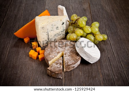 Delicious fresh french cheeses served on wooden table - stock photo