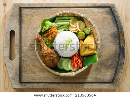 Delicious nasi ayam penyet with sambal belacan. Fried chicken rice with overhead view. Famous traditional Indonesian food. - stock photo