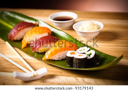 Delicious sushi rolls on the leaf with chopsticks and wasabi. Maki - stock photo
