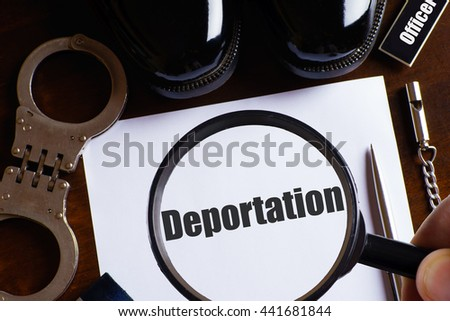 """""""Deportation"""" text with a man hold magnifying glass zoom on paper with pen, whistle, handcuff and a pair of black shoes on wooden table - law and enforcement concept - stock photo"""
