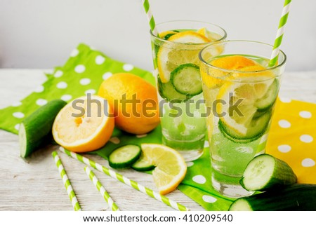 detox , healthy and refreshing drink ,Nutritious cold sparkling water with fresh green cucumber and yellow lemon on a wooden background - stock photo