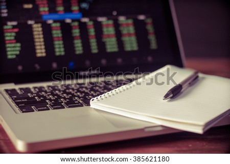 diary and  pen with computer notebook . stock chart on screenon wooden table.with copy space screen,morning light,vintage color,,Soft focus, selective focus  - stock photo