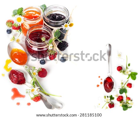 Different berry jam in jar and spoon - stock photo
