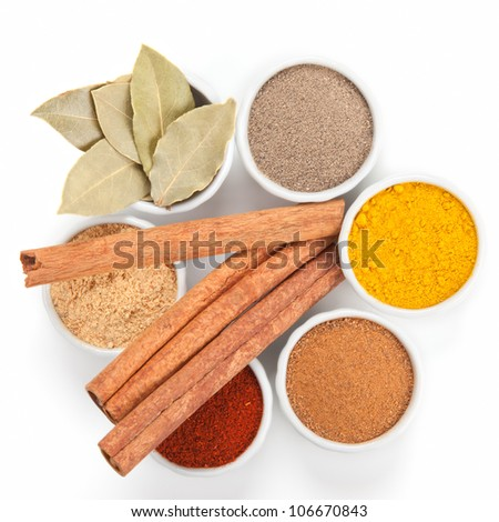 Different spices in white bowls isolated on white background. Paprika, Curry, Black Pepper, Ginger, Cinnamon, Bay Leaves.