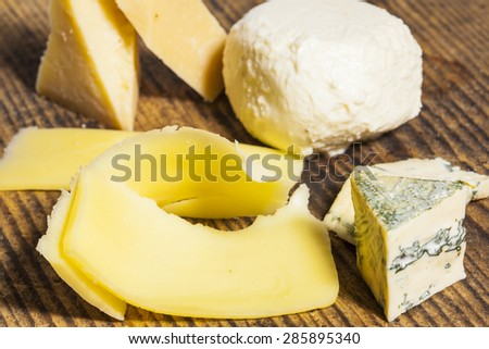 Different types of cheese on wooden table - pizza ingredients - stock photo