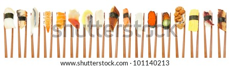 17 different types of sushi being held up in a row with wooden chopsticks isolated on white.