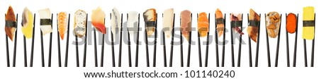 18 different types of sushi being held up in in a line with black chopsticks isolated on white.
