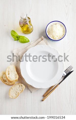 Dinner setting. White porcelain plate. Fresh sliced �¢??�¢??bread, olive oil, parmesan cheese. Italian cuisine. - stock photo