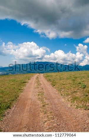 """Direct dirt road, on horizon hills, the dark blue sky and clouds"""