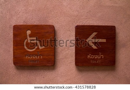Disabled toilet symbol and symbol for toilet on wooden texture. The background is a wall made ??of clay . - stock photo