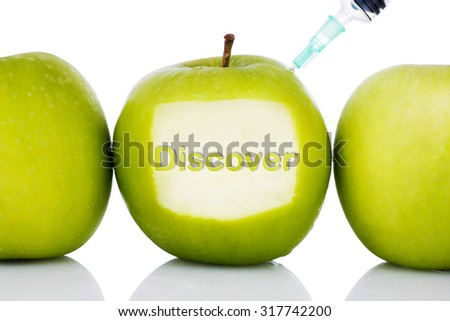 """""""Discover"""" text on green apple with syringe injected on it isolated white background - concept for genetically modified foods for diet,future health, science, chemistry, medicine and people. - stock photo"""