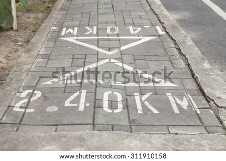 Distance signs on  floor in the park.