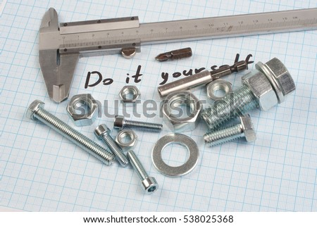 """Do it yourself"" - Screw, Nuts and caliper on graph paper background"