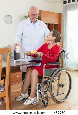doctor bringing up   disabled woman to the dinner table.