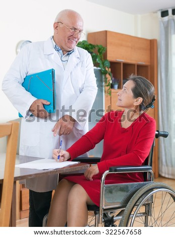 doctor discussing documents with disabled women.