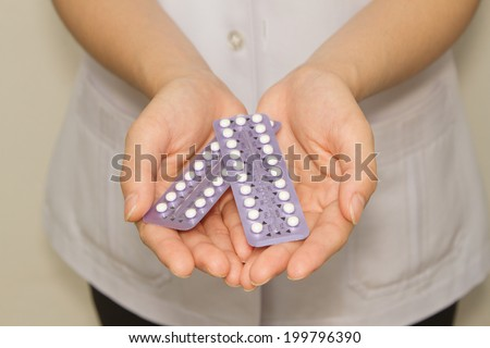 doctor's hand  holding the birth control pills  - stock photo