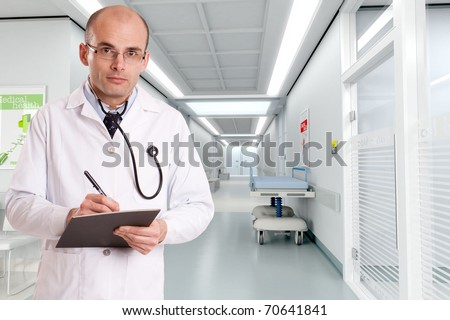 Doctor taking notes at the entrance of  a hospital corridor - stock photo