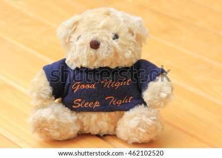 Doll bear brown on a wooden background