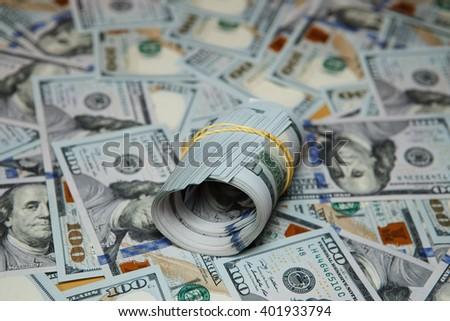 100 dollar bills. texture spilling hundred dollar bills. dollar roll on background of many dollars - stock photo