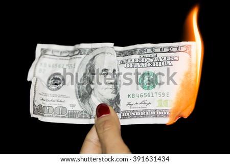 100 dollars burning on a black background - stock photo