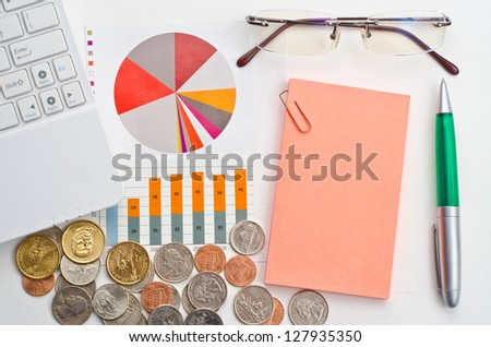 Dollars, computer, pen, glasses and graphs for finance concept - stock photo