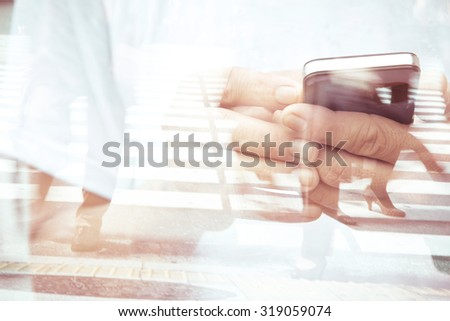 Double exposure of man using smart phone and people walking on street background